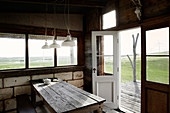 Wooden table with bench in rustic hut with limestone wall