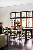 Wooden chairs on the massive table in the dining room in shades of brown