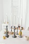 Autumnal arrangement of candlesticks, pumpkins and wooden discs on table