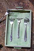 Artfully bent forks on wooden tray