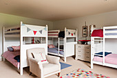 White wooden bunkbeds in childrens bedroom with armchair and decorative bunting