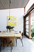 Hinged dining table with chairs in front of sliding patio door