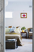 Glance into the bedroom with a double bed, bedside table and rattan chair