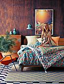 Junge Frau auf Doppelbett mit bunter Bettwäsche vor Holzwand