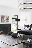 Living room with anthracite-colored furnishings: upholstered sofa, floor lamp by the window, pouf and coffee table in front of the fireplace