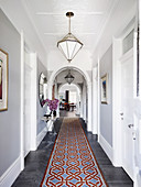 Long hallway with round arches, light gray wall, white doors and carpet runner