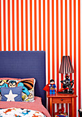 Bed with comic sheets and bedside table in front of striped wallpaper in boy's room