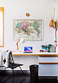 White desk above world map in home office