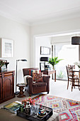 Brown leather armchair, side table, floor lamp and half-height cabinet in the living room