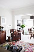 Brauner Ledersessel, Beistelltisch, Stehleuchte und halbhoher Schrank im Wohnzimmer