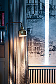 Wall-mounted lamp in front of striped curtain and window with shutters