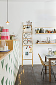 Festively decorated ladder in dining room next to open-plan kitchen