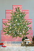 Picture of Christmas tree on red-and-white patterned panels on wall