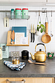 Book stand and various utensils hung above gold kettle on kitchen worksurface