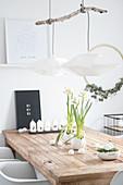 Holztisch mit Osterdekoration: Kerzen, Narzissen und Kresse-Nest mit weißen Eiern