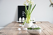 Easter arrangement of cress nest with white eggs, narcissus and candles on wooden table