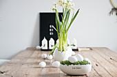 Holztisch mit Osterdekoration: Kresse-Nest mit weißen Eiern, Narzissen und Kerzen
