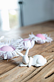 Bunny figurines and Easter eggs in handmade paper nests on wooden surface