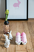 Pink eggs in egg rack, bunny figurines and hyacinth on wooden table