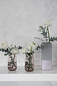 Ranunculus in concrete-effect vase handmade from milk carton and glass vases