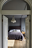 View into bedroom in shades of grey through open double doors