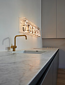 Illuminated lettering above sink in minimalist kitchen