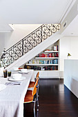 Laid dining table with classic chairs, stairs and bookcase in the background