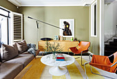 Cognac-colored leather chairs, classic table, sofa and sideboard in the living room with green walls