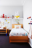 Wooden bed with colorful bedclothes, a shelf with play figures in the children's room