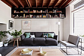 Gray upholstered sofa, bookshelf above in the living room with wooden beam ceiling