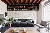 Graues Polstersofa, darüber Bücherregal im Wohnraum mit Holzbalkendecke