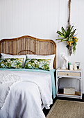 Rattan bed with headboard, bedside table and plant decoration in the bedroom