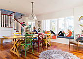 Long dining table with colorful chairs in an open living room with stairs, family in the room