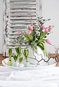 Tulpenstrauß in Kugelvase und Hyazinthen mit gewachsten Blumenzwiebeln als Frühlingsdeko
