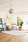 Kunstwerke und Staffelei in hellem Atelier, Frau auf Fensterbank sitzend
