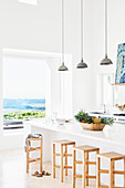 Kitchen counter with wooden bar hoppers and pendant lights in the background window with sea view