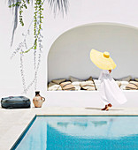Frau mit Hut in weißem Kleid am Pool