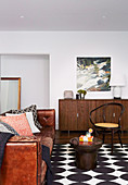 Vintage leather couch, coffee table, chair and sideboard in the living room with black and white carpet