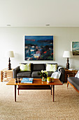 Gray sofa set, side tables with table lamp and coffee table in the living room, works of art on the wall