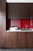 Fitted wardrobe with dark fronts and red back wall in the bathroom