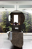 Basalt washbasin and wall mirror in front of glass wall