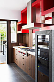 Kitchenette with wooden fronts and built-in appliances, red shelf above as a room divider