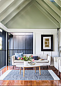 Bright upholstered sofa and coffee table in the living room with a gable roof