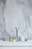 Osterhase und Eier vor grau verputzter Wand