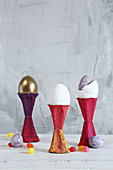 Easter eggs in eggcups made from painted egg box sections