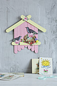 Birdhouse decoration made from painted lolly sticks and scrapbook pictures