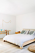 Solid wood double bed and console in white bedroom