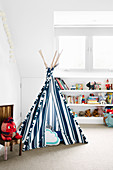 Blue and white striped tipi in front of a shelf in a white children's room
