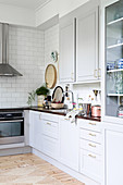 Scandinavian country-house kitchen in white and grey with wooden floor