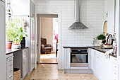 Country-house kitchen in white and grey with subway tiles and wooden floor